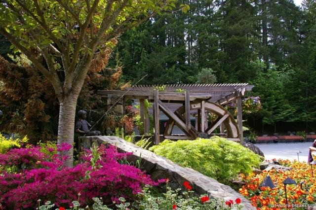 Statue of boy fishing and water mill at Butchart Gardens in Victoria.jpg