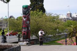Bagpipe player next to totem pole in Victoria.jpg